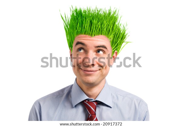 Happy young businessman looking up at his new vivid green grass hair. Green business concept