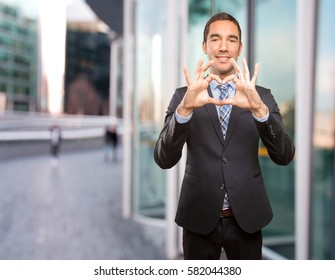 Happy young businessman with a love gesture