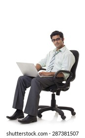 Happy young businessman on chair using laptop