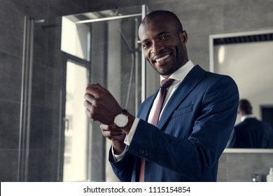 happy young businessman putting on his wristwatch at bathroom
