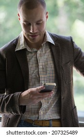 Happy young businessman reading text message on smartphone
