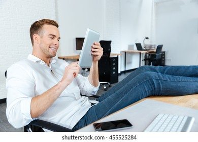 Happy young businessman sitting with legs on table and using tablet at workplace