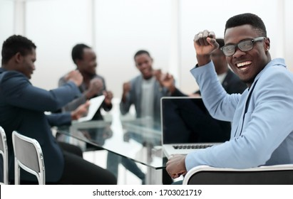 happy young businessman sitting at office Desk