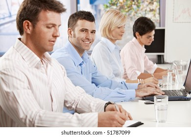 Happy young businessman sitting on business meeting with colleagues at office, looking at camera, smiling.