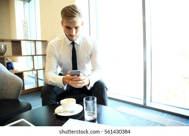 Happy young businessman sitting relaxed on sofa at hotel lobby using smartphone, waiting for someone.