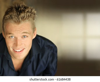 Happy young businessman smiling against neutral background with lots of copy space