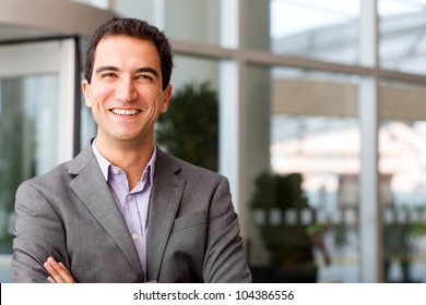 Happy young businessman smiling at the office