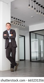 Happy young businessman standing in office hall