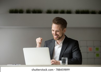 Happy young businessman in suit looking at laptop excited by good news online, lucky successful winner man sitting at office desk raising hand in yes gesture celebrating business success win result