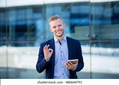 Happy young businessman with the tablet shows ok on a background of blue glass building