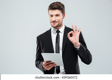 Happy young businessman with tablet winking and showing ok sign over white background