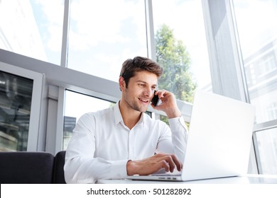 Happy young businessman talking on cell phone and using laptop in office