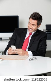 Happy young businessman using cell phone at desk in office