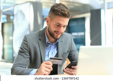 Happy young businessman using laptop and credit card at the table.