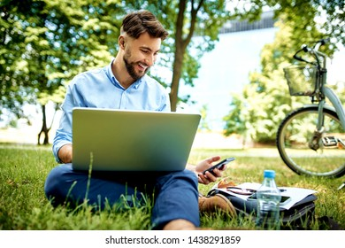 Happy young businessman using laptop and phone while sitting in the park during lunch break