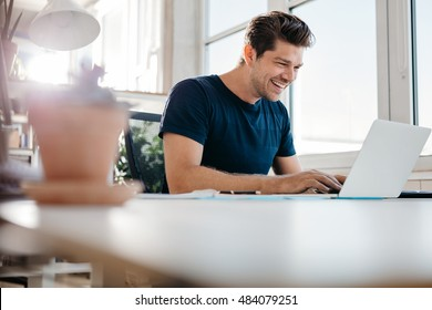 Happy young businessman using laptop at his office desk. Young male executive working on laptop at his desk.
