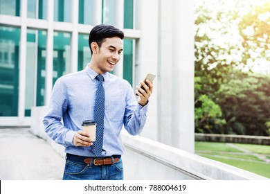 Happy Young Businessman using a Smart Phone outdoor, Communicate Technology in Business Concept, Lifestyle of Modern Male