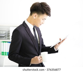 happy young  businessman watching tablet in office