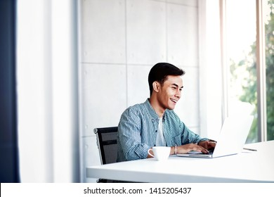 Happy Young Businessman Working on Computer Laptop in Office. Sitting on Desk, Man in Casual Wear