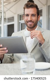 Happy young businessman working on tablet drinking espresso in patio of restaurant