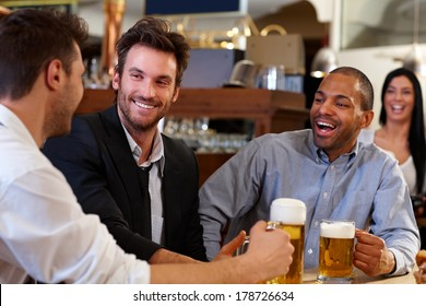 Happy young businessmen drinking beer and talking at pub after work. Looking at each other smiling.