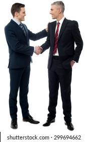 Happy young businessmen shaking hands over white