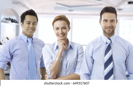 Happy young businesspeople in blue shirt at international office.