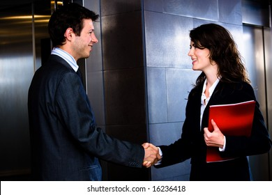 Happy young businesspeople - businessman and businesswoman - shaking hands at office corridor in front of elevator, smiling.