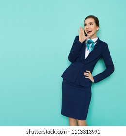 Happy young businesswoman in blue suit and turquoise scarf is standing with hand raised, shouting and looking away. Three quarter length studio shot on turquoise background.