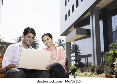 Happy young businesswoman and businessman using laptop outdoors