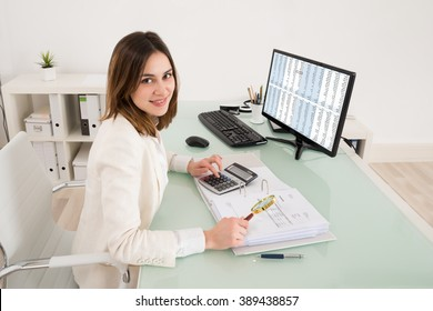 Happy Young Businesswoman Checking Invoice With Magnifying Glass