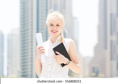 Happy young businesswoman in the city