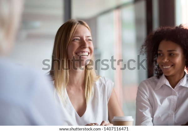Happy young businesswoman coach mentor leader laughing at funny joke at group business meeting, joyful smiling millennial lady having fun with diverse corporate team people engaged in talking at work