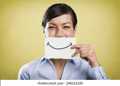 Happy young businesswoman holding blank white card with space for text in front of her mouth, isolated on yellow background.
