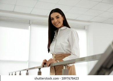 Happy young businesswoman leaning on railing in office