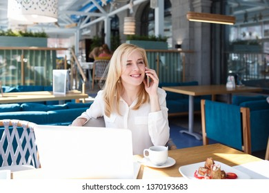Happy young businesswoman or manager of large company talking on the phone with friends or colleagues discussing plans for the weekend sitting at table in cafe with laptop.