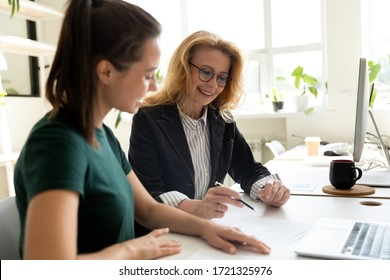 Happy young businesswoman presentation project using laptop for mature female mentor in boardroom at meeting. Smiling leader presenting new business concept for woman colleague discuss.