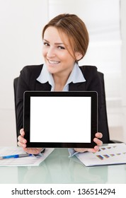 Happy Young Businesswoman Presenting Digital Tablet In The Office
