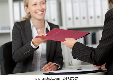 Happy young businesswoman receiving file from coworker at office desk