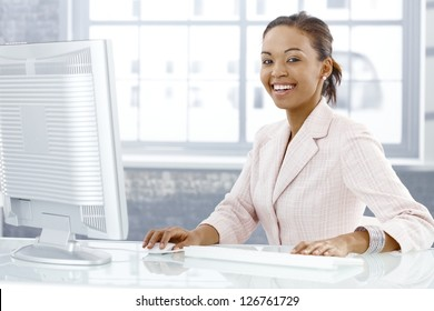 Happy young businesswoman sitting at desk, working on computer, laughing at camera.