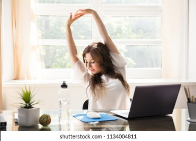 Happy Young Businesswoman Stretching Her Arms In Office