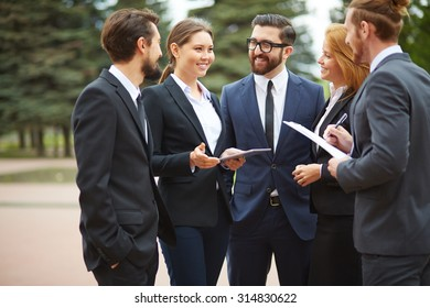 Happy young businesswoman talking to colleagues at meeting