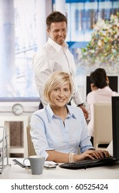 Happy young businesswoman using computer in bright office, colleagues working in the background.?