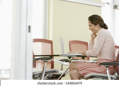 Happy young businesswoman using laptop in conference room