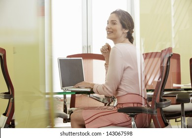Happy young businesswoman using laptop in meeting room