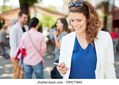 Happy young businesswoman using mobilephone in the city.