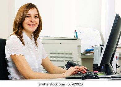 Happy young businesswoman working on computer.