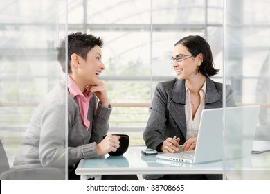 Happy young businesswomen working together at desk in modern office, looking at each other, laughing.