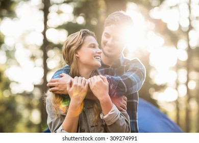 Happy young camper couple looking at each other in the nature