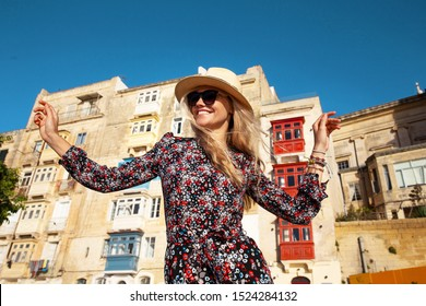 Happy young carefree woman enjoying sightseeing in Valletta, Malta, Europe